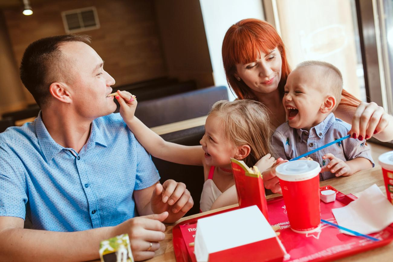 Happy family eating in fast food restaurant