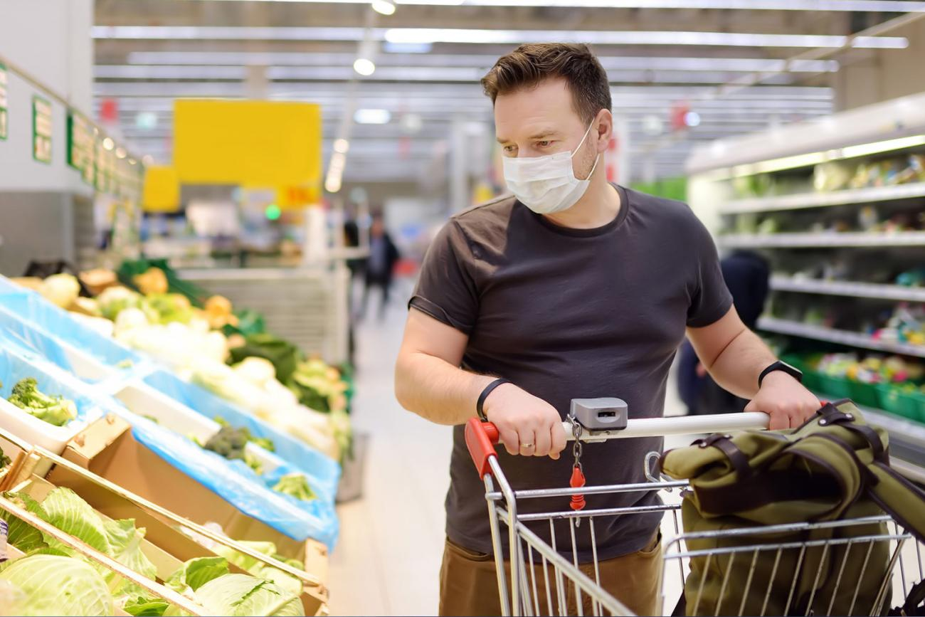 Man shopping in grocer store wearing mask